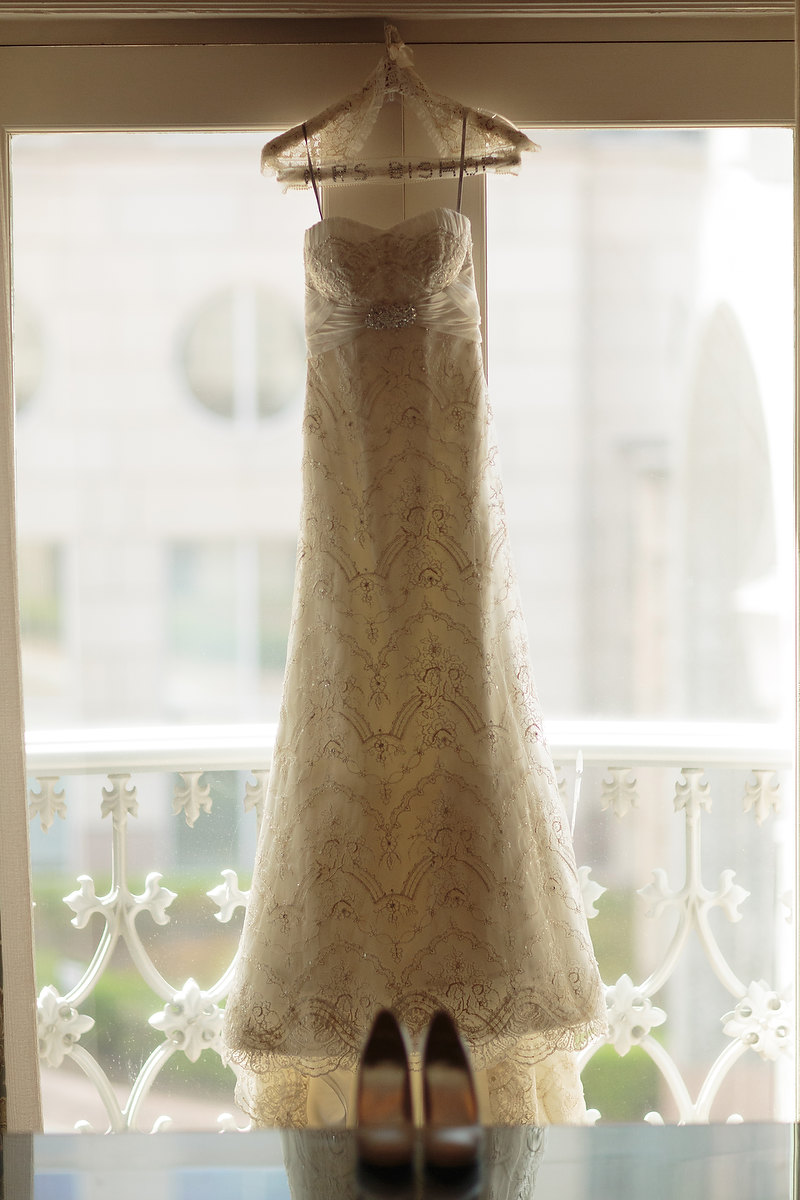 Beaded strapless wedding gown hanging on personalized clothes hanger in a window at The Crescent Hotel in Dallas, TX - Photo by Joseph Mark Photography