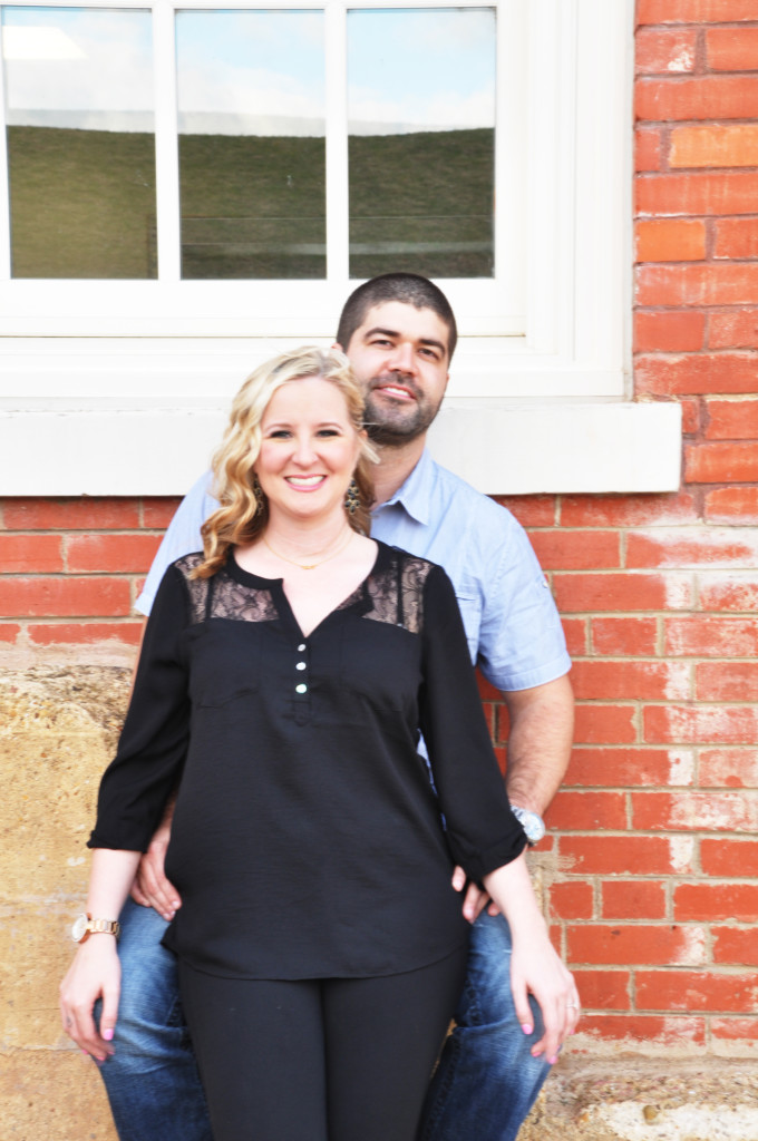 Outdor engagement pictures with red brick building - Photo by Jennifer Long