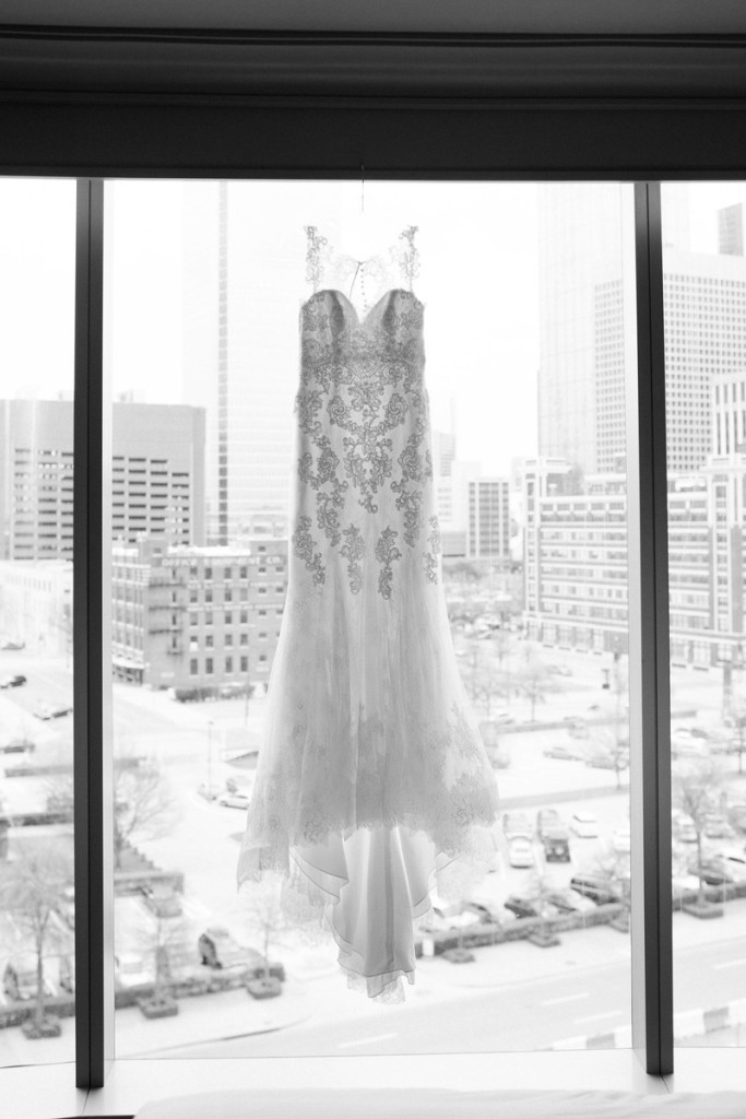 Lace wedding dress hanging in window with city buildings in background Photo by Laura Elizabeth Photographers