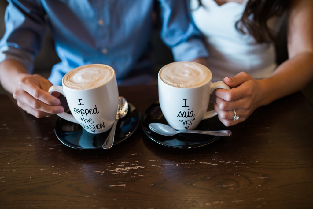 Coffee shop engagement pictures with I popped the quetstion and I said yes coffee mugs - Photo by Texas Sweet Photography