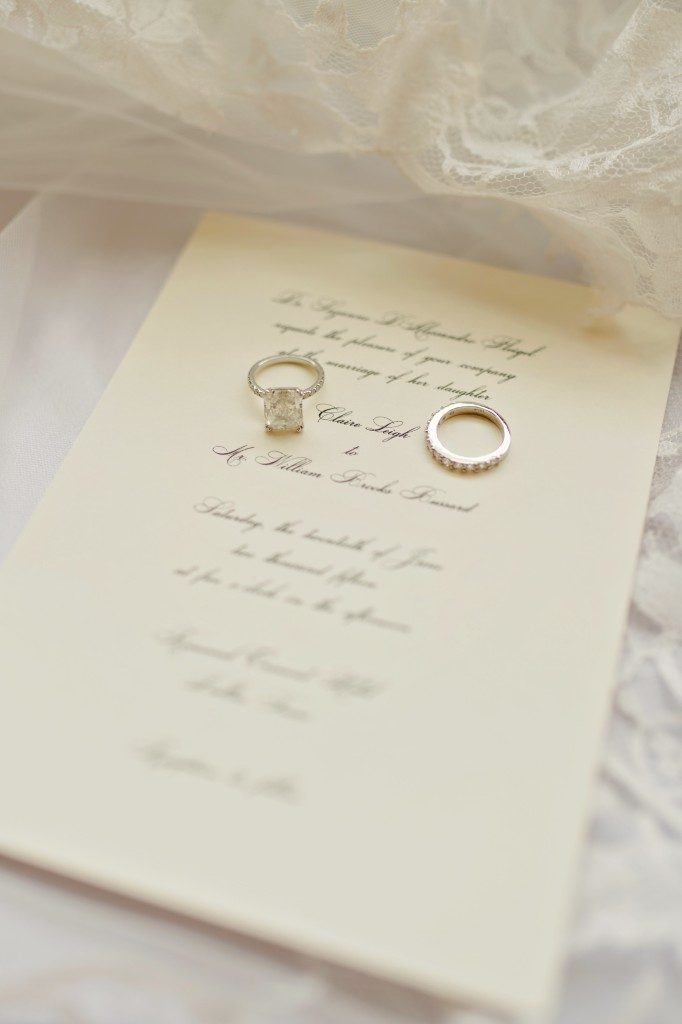 Wedding rings on traditional wedding invitation resting on lace veil - Photos by Celina Gomez Photography