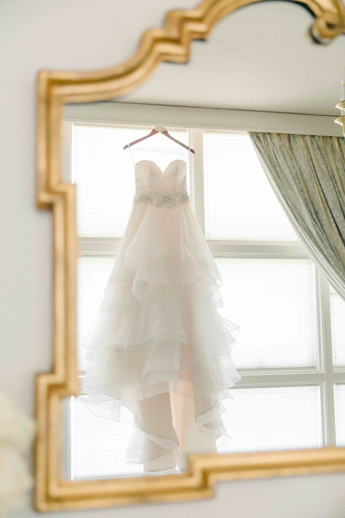 Gold mirror view of brides white strapless wedding dress hanging before summer wedding ceremony - Photo by Arden Prucha Photography