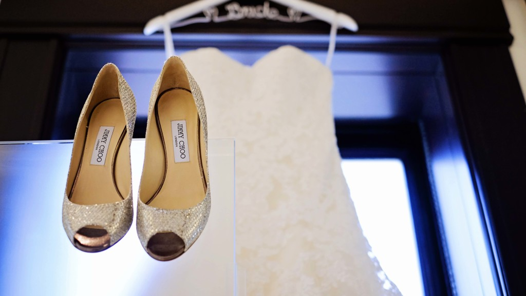 Strapless lace dress hanging on custom personalized bridal wedding dress hanger with silver open toed Jimmy Choo heels - Photo by Jenny & Eddie