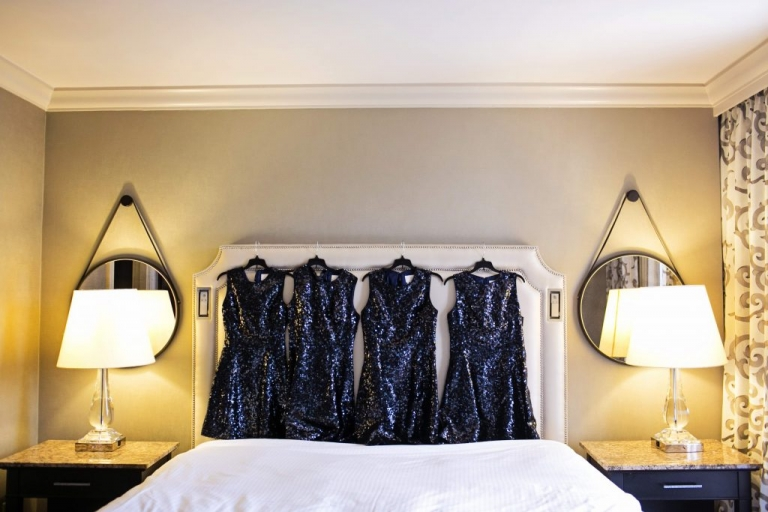 Four short navy sequin bridesmaids dresses hanging on bed in hotel room before August wedding - Photo by Jenny & Eddie