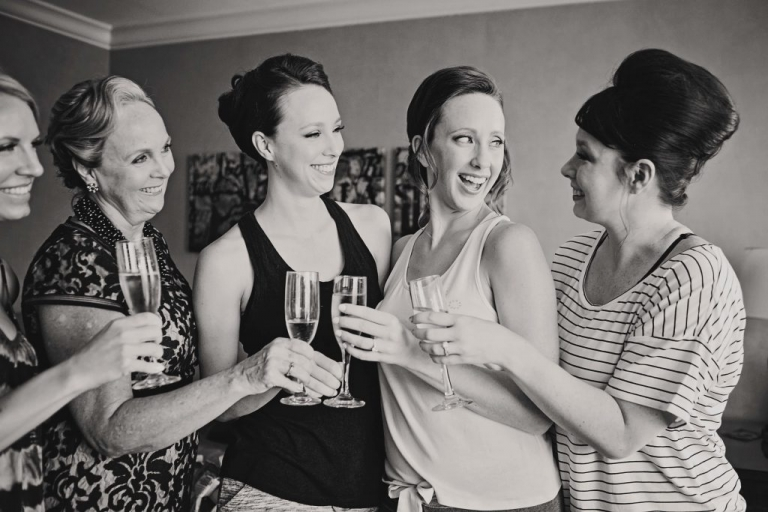 Bride and bridesmaids toasting with champagne while getting hair and makeup done - Photos by Jenny & Eddie