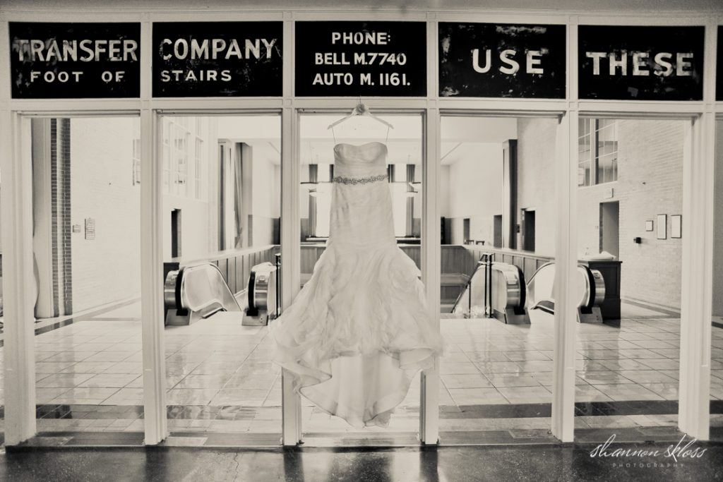 Strapless wedding dress with beaded belt hanging in old train station Union Station in Dallas, TX fall wedding - Photos by Shannon Skloss Photography