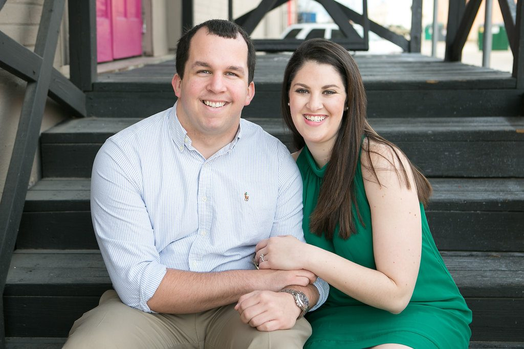 Outdoor engagement photos couple sitting on stairs bride in green dress - Photos by The Mamones