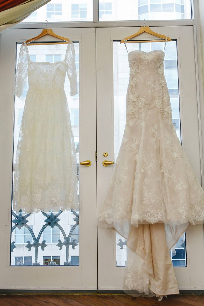 Brides wedding ceremony and reception dress hanging in doorway before fall wedding at Perot Museum in Dallas, Texas - Photos by Katherine O'Brien Photography