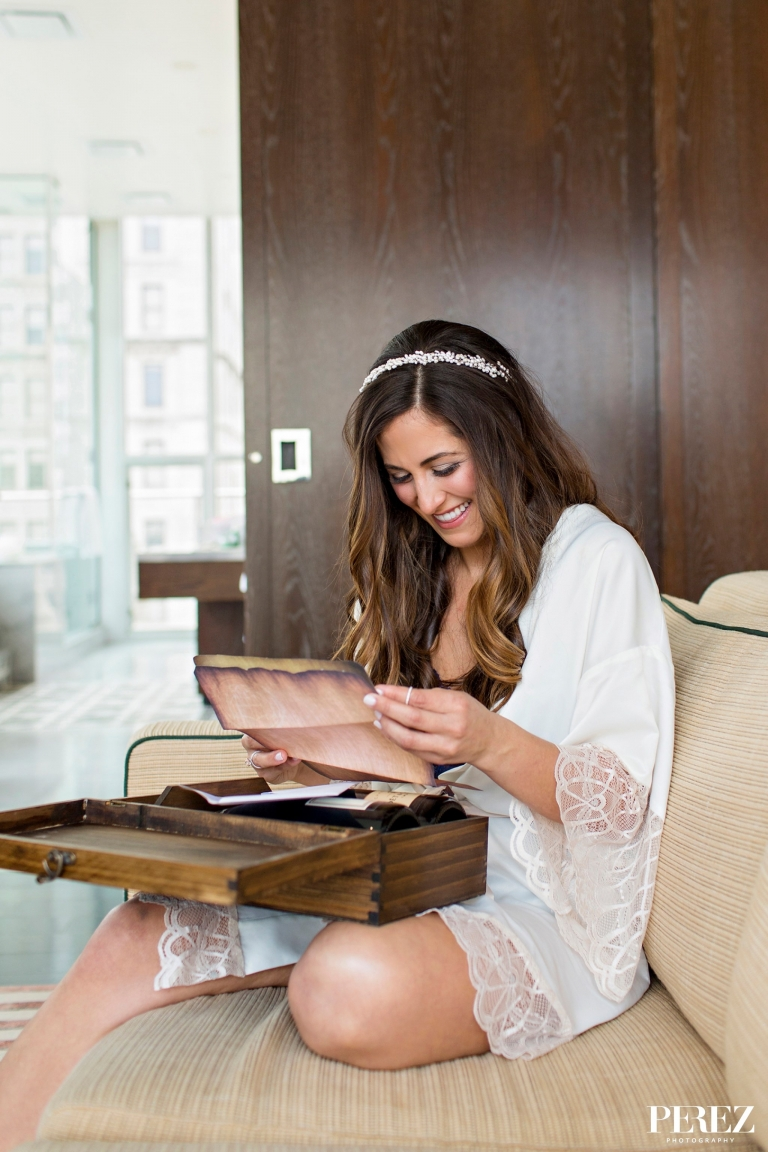 Bride opening gift and reading letter from groom before winter wedding in Dallas, Texas - Photos by Perez Photography