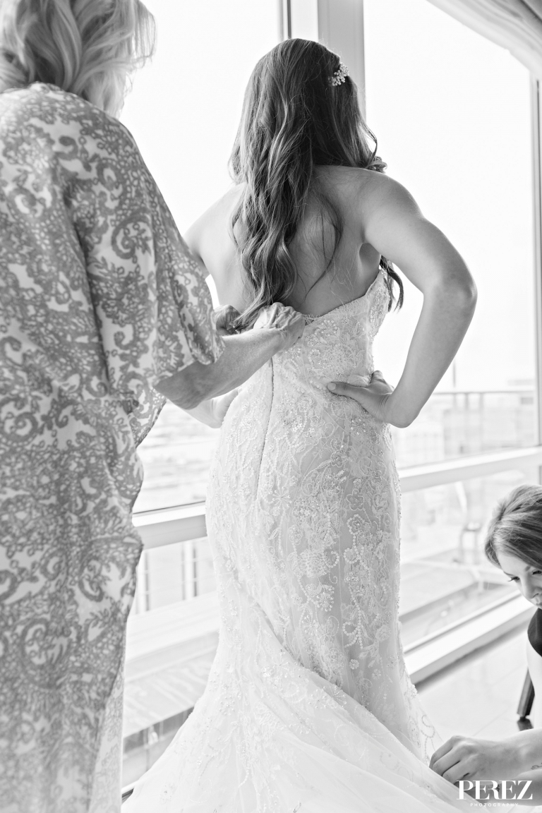 Mother of the bride zipping up brides lace wedding dress before formal winter wedding ceremony at The Joule Hotel in Dallas, Texas - Photos by Perez Photography