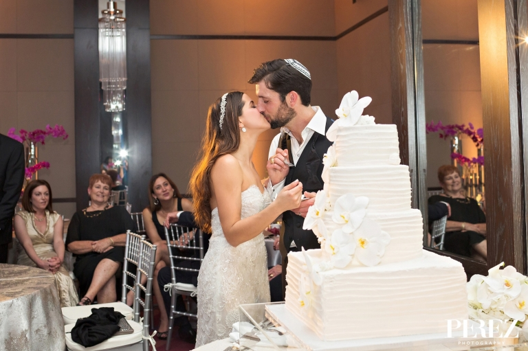 Bride and groom cake cutting sharing a kiss at winter Jewish wedding reception at The Joule Hotel in Dallas, Texas - Photos by Perez Photography