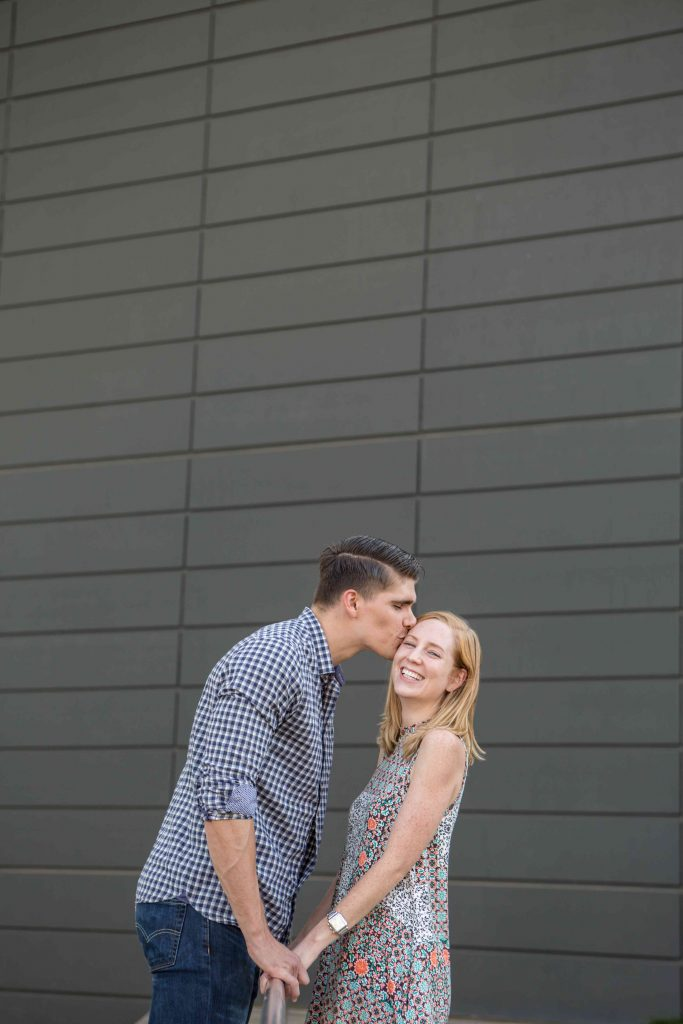 Outdoor engagement photos next to grey wall in Dallas, Texas - Photos by RAP Photography