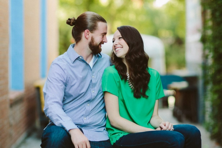 Couple sitting on bench for outdoor engagement photos in Dallas, Texas - Photos by Honey and Salt Photography