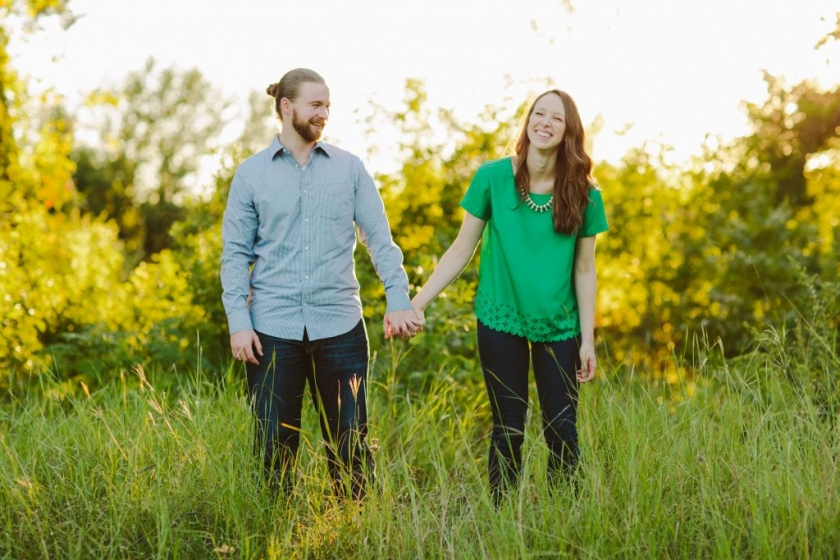 Couple holding hands and laughing during outdoor engagement photos in field in Dallas, Texas - Photos by Honey and Salt Photography