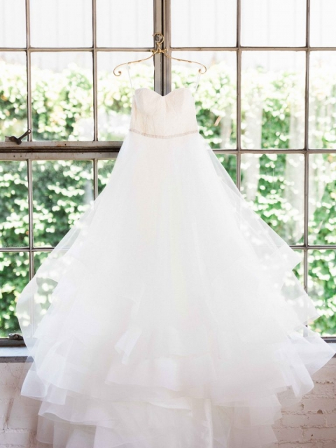 White strapless tiered ballgown with small embellished belt bridal gown hanging in window for summer wedding at Hickory Street Annex in Dallas, TX - Photos by Elisabeth Carol Photography