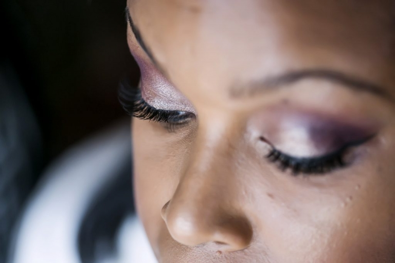 African american bride with gorgeous purple eyeshadow getting ready before summer wedding renewal ceremony in Dallas, Texas - Photos by Jenny & Eddie