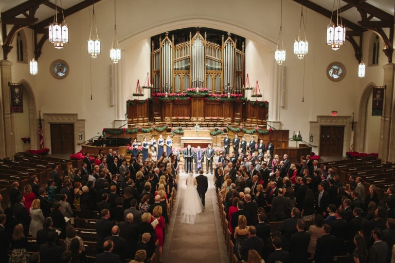 Winter wedding ceremony with red poinsettias in Park Cities Presbyterian Church in Dallas, Texas