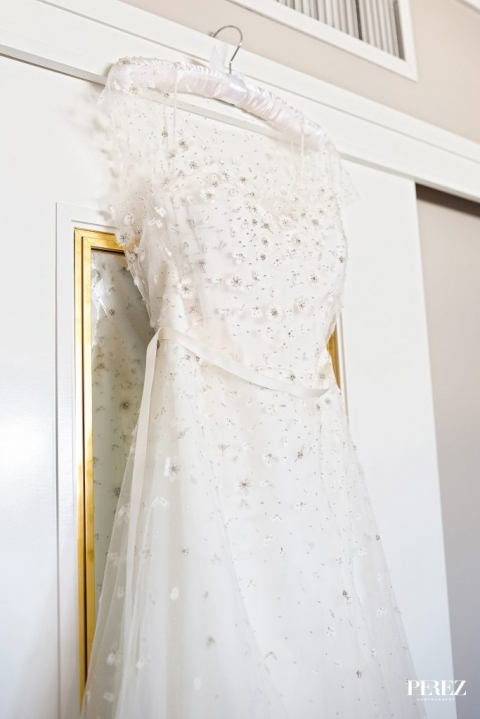 Bride wedding dress with floral accents hanging on white satin hanger before spring wedding in Dallas, Texas - Photos by Perez Photography