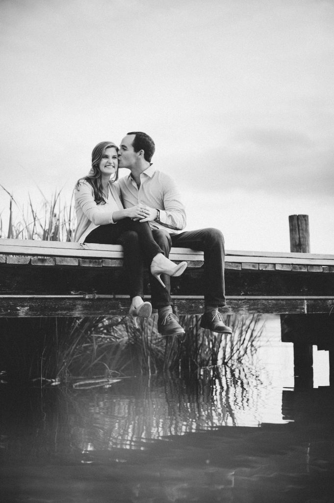 Outdoor engagement photos couple sitting on a dock at the lake - Photos by Rae Portraits