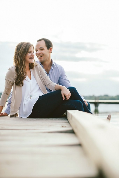 Outdoor engagement photos in Dallas, Texas couple sitting on dock at lake - Photos by Rae Portraits