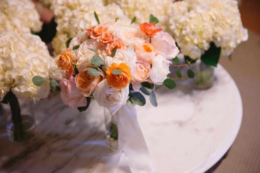 Spring wedding bouquets with white hydrangeas and pink and orange roses - Photo by Evan Godwin Photography