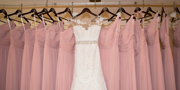 Brides dress and long pink bridesmaid dresses hanging on monogrammed hangers bridesmaid gift ideas for summer wedding in Dallas, TX - Photos by The Mamones