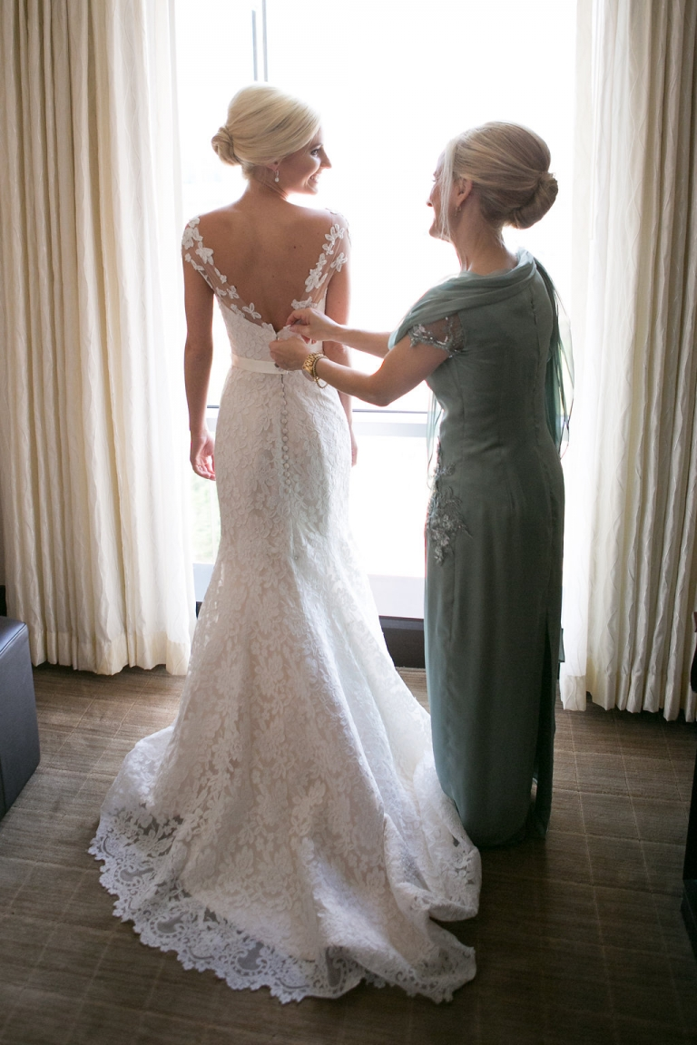 Mom zipping up brides dress before summer wedding ceremony in Dallas, TX - Photos by The Mamones
