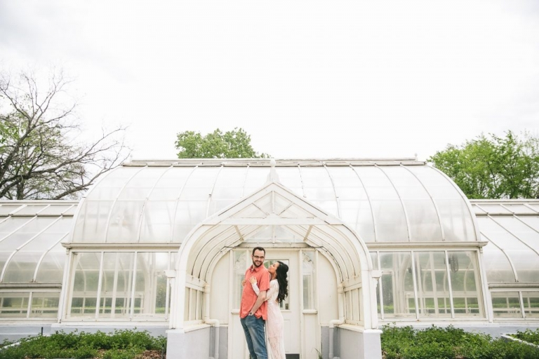 Outdoor engagement photo shoot inspiration couple in front of greenhouse - Photos by Andrew Chan Weddings