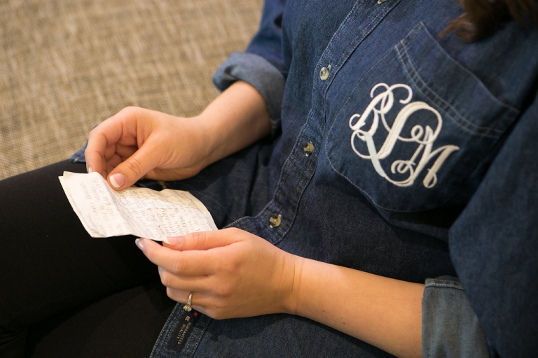 Bride reading a note from the groom in a custom monogrammed denim button down shirt - Photos by The Mamones