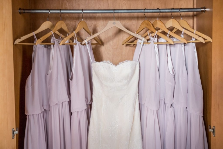 Brides dress hanging with bridesmaids lavender dresses - Photo by Rap Photo Company