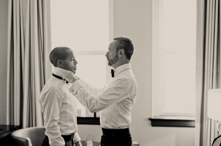 Two grooms getting dressed before winter wedding ceremony at The Joule Hotel - Photo by Shannon Skloss Photography