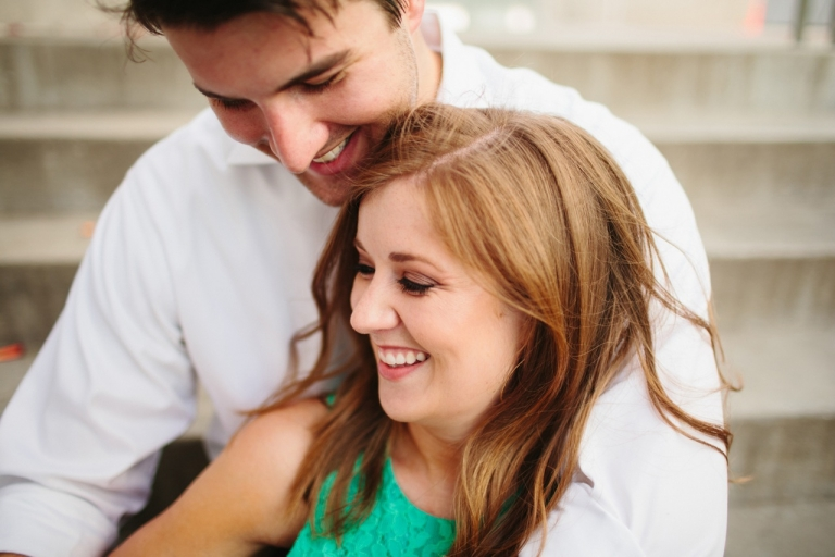 Couple sitting on stairs for outdoor engagement photos - Photo by Sara & Rocky Photography
