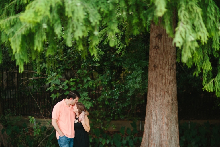 Couple standing under large tree for outdoor engagement photos in Dallas - Photo by Sara & Rocky Photography