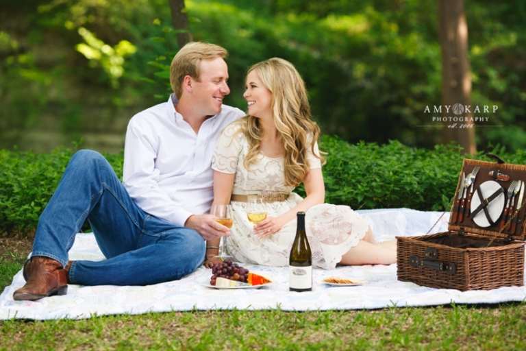 Outdoor engagement photos with couple sitting on a blanket drinking wine and eating cheese - Photo by Amy Karp Photography