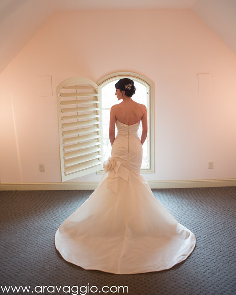Bride standing in front of window in home of at-home wedding - Photo by Aravaggio Photography