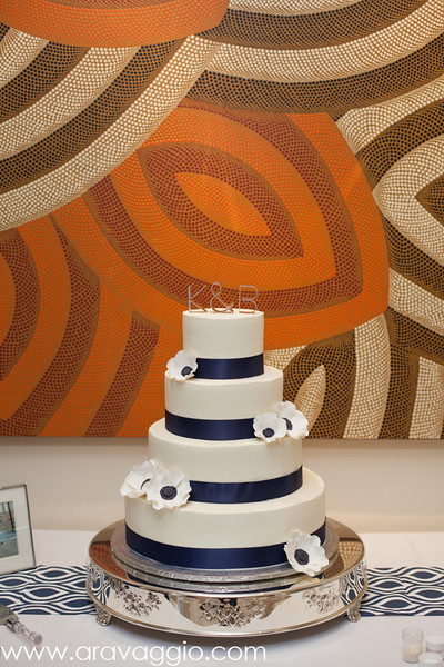 Four tiered white wedding cake with navy ribbons - Photo by Aravaggio Photography