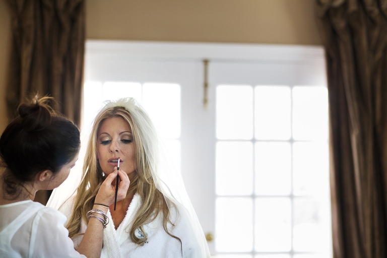 Bride in white robe and veil having makeup touch ups - Photo by helmutwalker photography