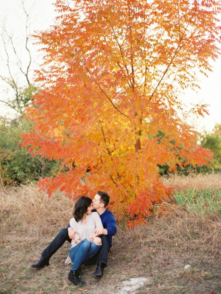 Fall outdoor engagement photos couple sitting in field by beautiful orange tree - Photo by Joshua Aull Photography
