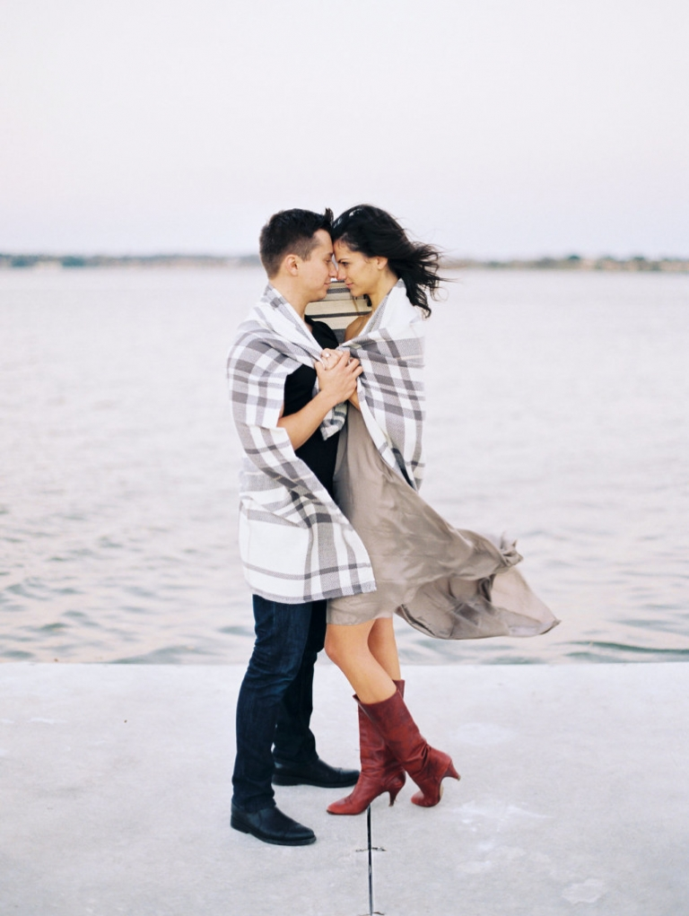Fall outdoor engagement photos couple standing by lake wrapped in a blanket - Photo by Joshua Aull Photography