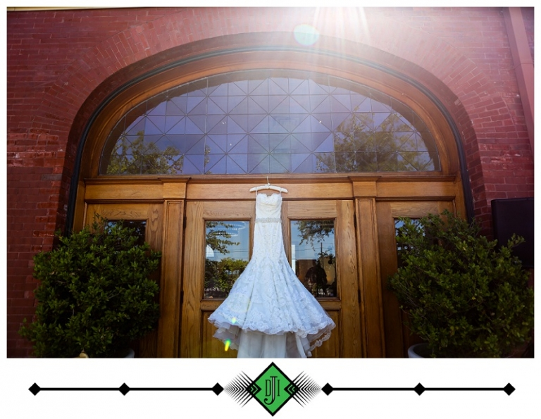 Brides strapless wedding dress hanging on a satin clothes hanger outside on wood doors on a red brick building - Photo by Devon J. Imagery