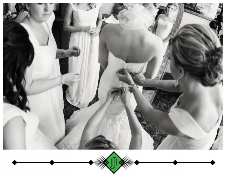 Bridesmaids helping bride button up dress - Photo by Devon J. Imagery