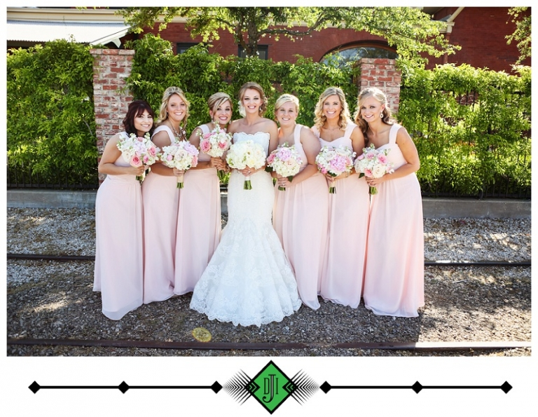 Bride and bridesmaid posing outside bridesmaids in light pink dresses with straps - Photo by Devon J. Imagery