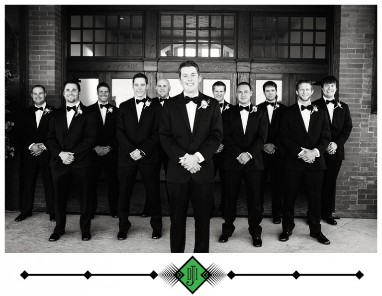 Black and white photo of groom and groomsmen in tuxedos with boutonnieres - Photo by Devon J. Imagery