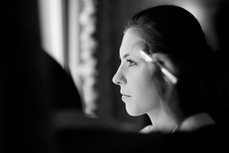 Black and white photo of bride having her makeup done - Photo by Joseph Mark Photography