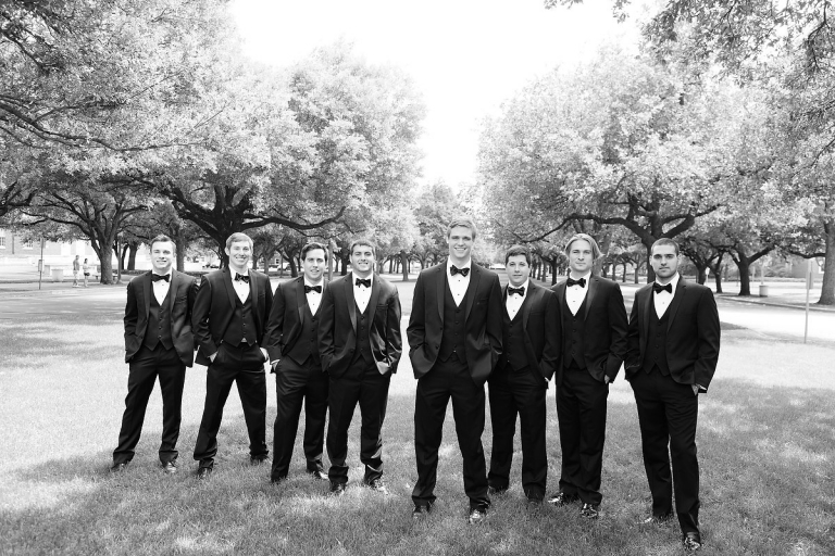 Black and white photo of groom and groomsmen in tuxedos on the Southern Methodist University campus - Photo by Joseph Mark Photography