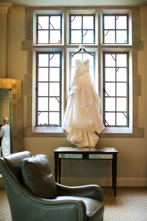 Wedding dress hanging in church window - Photo by Jenny Martell Photography