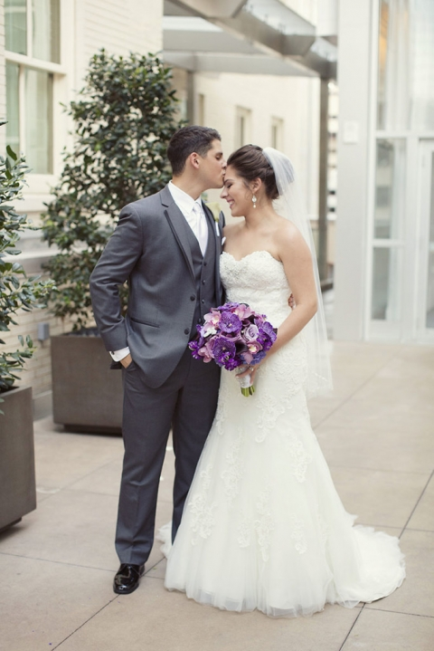 August wedding at The Joule in Dallas, TX groom in grey tuxedo bride in strapless gown with short veil and all purple wedding bouquet - Photos by Sarah Kate