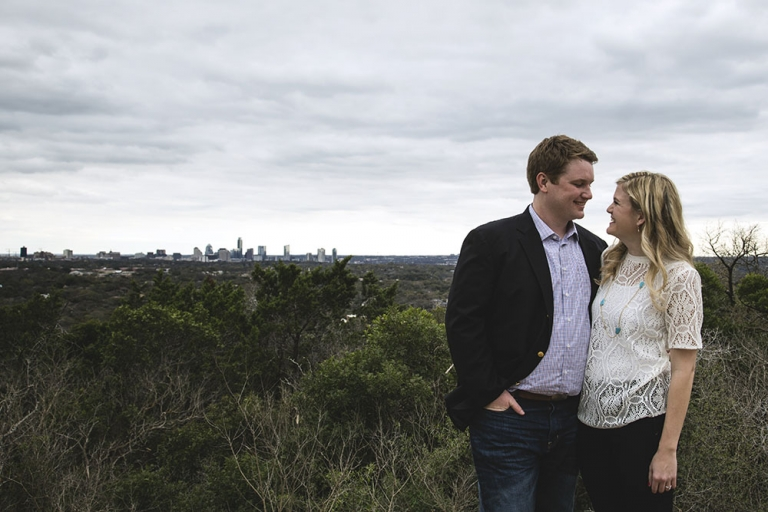 Outdoor engagement photo with city skyline - Photo by Nathan Lewis Photography