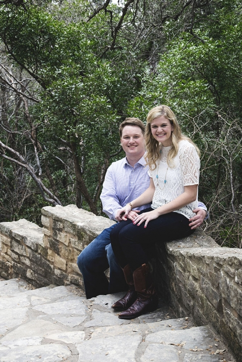 Outdoor engagement photo sitting on rock wall - Photo by Nathan Lewis Photography