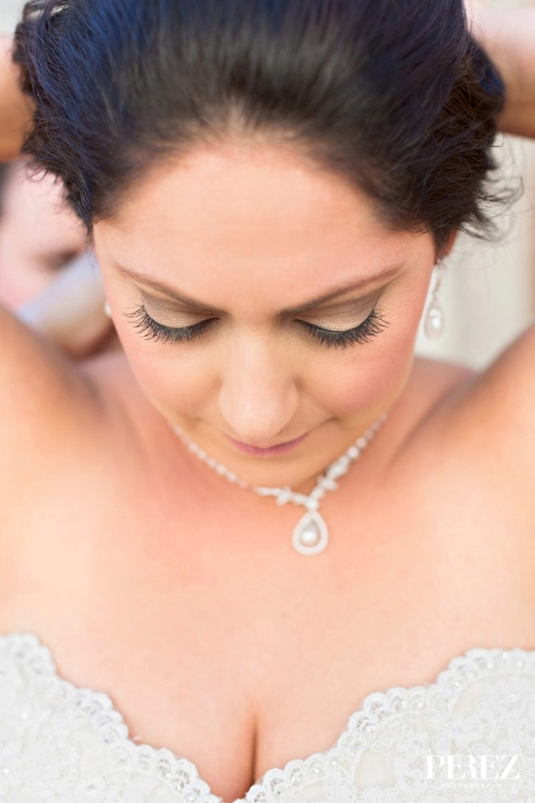 Bride putting on diamond necklace - Photo by Perez Photography